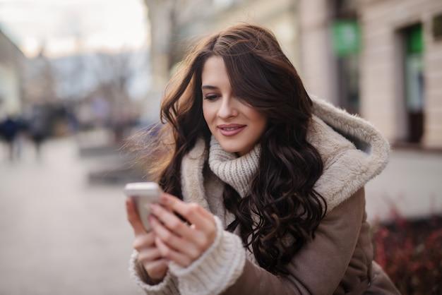 屋外で座って、メッセージを読んだり書いたりしてコートに長い茶色の髪を持つ豪華な白人女性のクローズアップ。