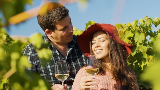 와인 잔을 손에 들고 서로 껴안은 멋진 커플의 클로즈업.