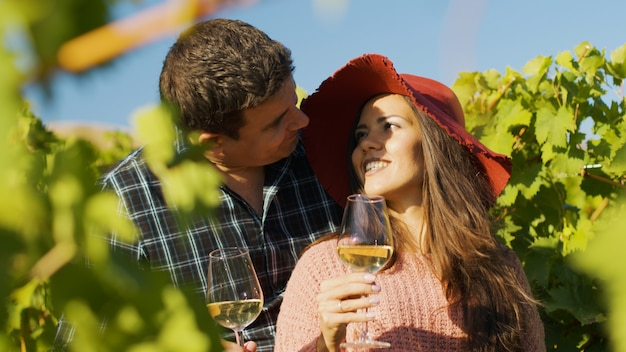 グラスワインを手に持って抱き合うゴージャスなカップルのクローズアップ。