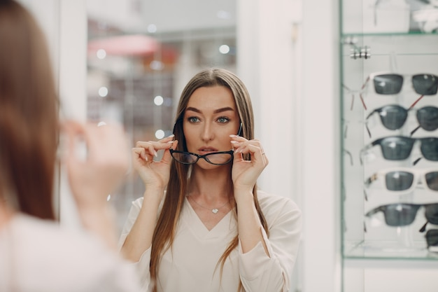 Крупным планом великолепная молодая улыбающаяся женщина, улыбаясь, выбирая и выбирая очки в углу оптики в торговом центре, счастливая красивая женщина, покупающая очки у окулиста