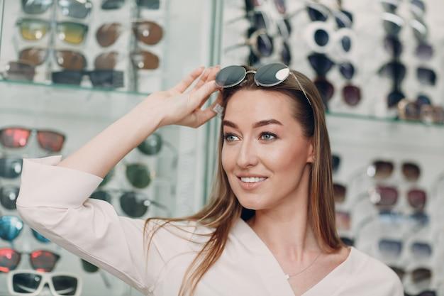 Крупным планом великолепная молодая улыбающаяся женщина улыбается, выбирая и выбирая очки в углу оптики в торговом центре. счастливая красивая женщина, покупающая очки у окулиста