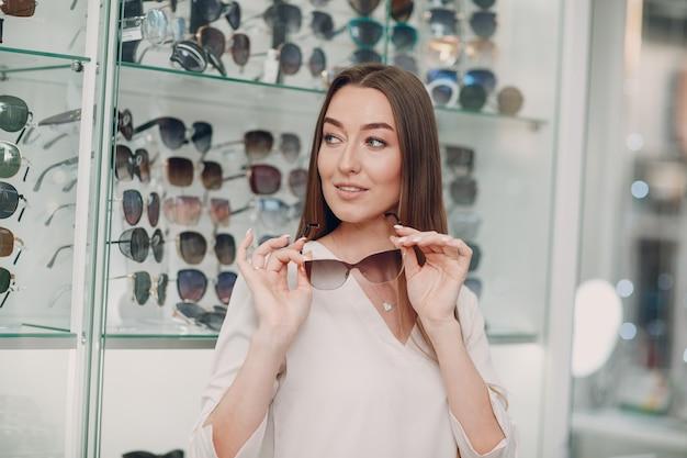 Крупным планом великолепная молодая улыбающаяся женщина улыбается, выбирая и выбирая очки в углу оптики в торговом центре.