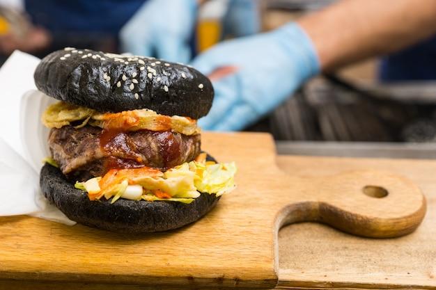 Крупным планом гамбургер для гурманов, подаваемый на деревянной разделочной доске с копией пространства и людьми в фоновом режиме