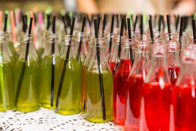 Крупным планом изысканные красные и зеленые газированные напитки в стеклянных бутылках с черной трубочкой