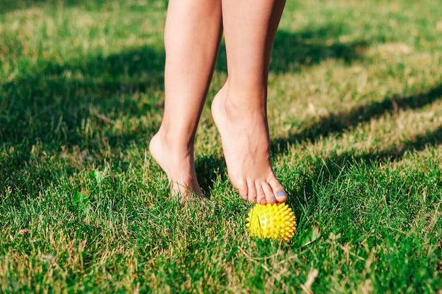 안뜰 여름, 물리 치료 개념의 녹색 잔디에 스파이크 마사지 공에 발끝에 서 있는 젊은 여성의 우아한 맨발의 클로즈업.