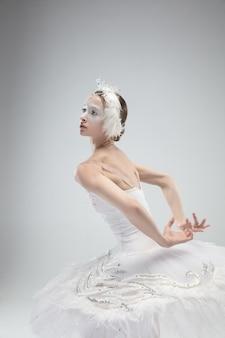 白い背景の上で踊る優雅な古典的なバレリーナのクローズアップ。