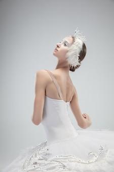 白いスタジオの背景に踊る優雅な古典的なバレリーナのクローズアップ。白鳥のような優しい服を着た女性。優雅さ、芸術家、動き、行動、動きの概念。無重力に見えます。