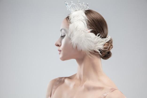 白いスタジオの背景に優雅な古典的なバレリーナのクローズアップ。白鳥のキャラクターのような優しい服を着た女性。優雅さ、芸術家、動き、行動、動きの概念。無重力に見えます。