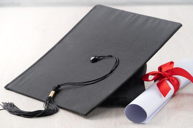 Закройте выпускной квадратный академический колпак с дипломом на фоне деревянного стола.