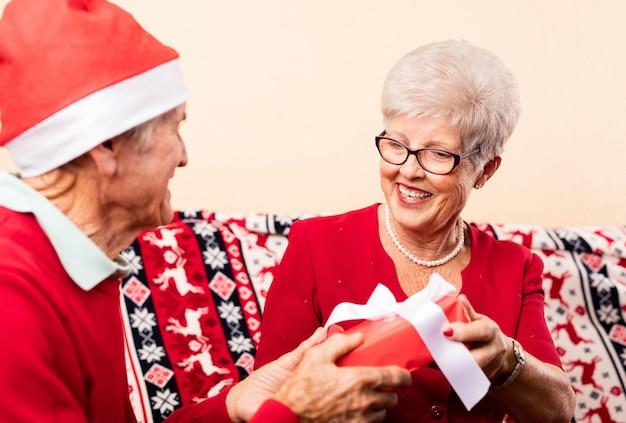 Крупным планом бабушки и дедушки, давая рождественские подарки