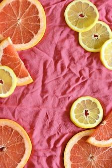 Крупный план рамки грейпфрута и лимона, с коралловым, розовым, красным фоном ткани, с копией пространства