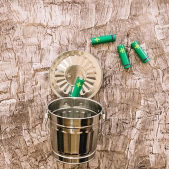 금속 쓰레기통에 녹색 배터리의 클로즈업