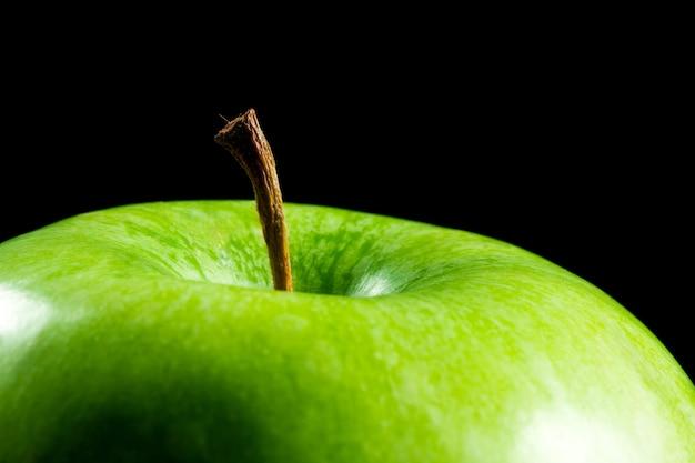 黒で分離された緑の熟したリンゴのクローズアップ