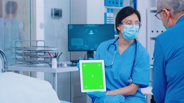 현대적인 개인 병원이나 진료소에서 녹색 화면 태블릿을 닫습니다. 앱, 텍스트, 비디오 또는 디지털 자산에 대한 가젯의 격리된 모형 크로마 교체 화면입니다. 쉬운 키잉 의학 의료 관련