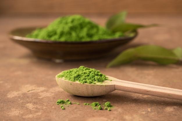 Закройте зеленый чай порошок в деревянной ложкой на столе.