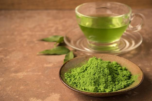 Закройте зеленый чай порошок со стеклянной чашкой горячего чая на столе. свободное место для текста
