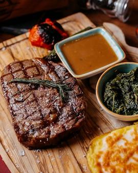 Крупным планом на гриле стейк из говядины с запеченным картофелем и соусом на деревянной доске