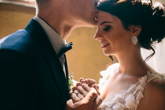 Close-up of groom kissing bride's forehead