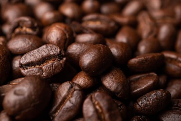 グループブラックコーヒー豆のクローズアップ。濃い黒のエスプレッソ、コーヒーの背景、テクスチャーの根拠