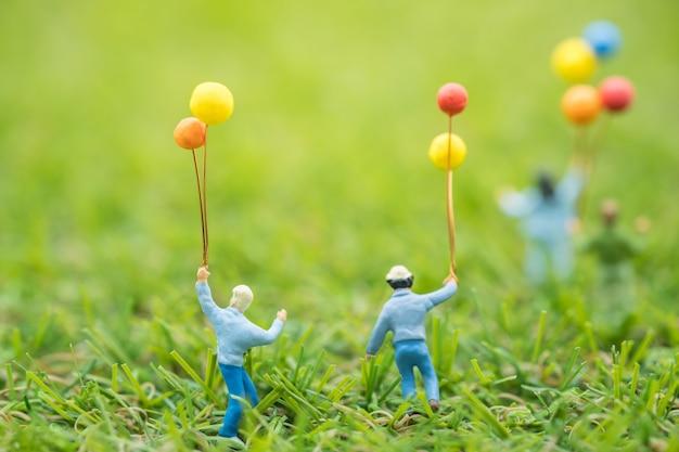 Закройте группу детей миниатюрных фигур людей, бегущих и играющих с воздушным шаром