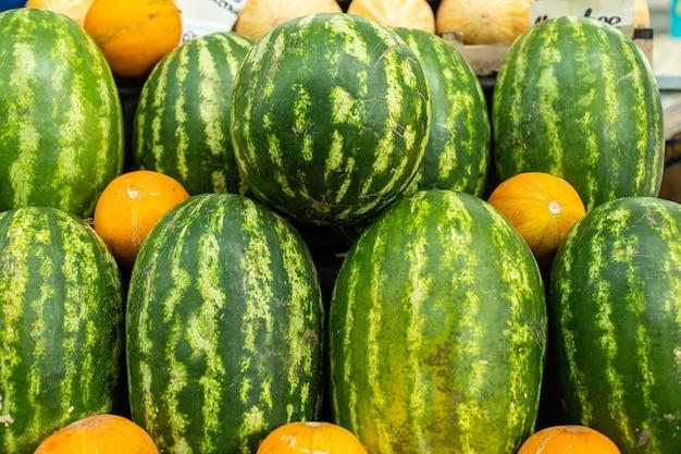 有機農場で販売する準備ができている新鮮な緑のスイカと黄色の甘いメロンのグループのクローズアップ。新鮮な果物のコンセプト