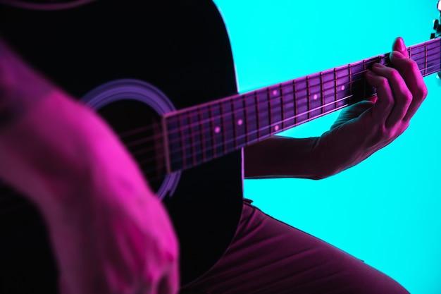 Закройте руки гитариста, играя на гитаре, макросе. концепция рекламы, хобби, музыки, фестиваля, развлечений. человек импровизирует воодушевленный. copyspace для вставки изображения или текста. красочный неоновый свет.