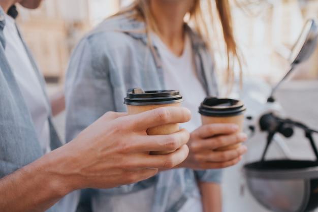 コーヒーのカップを保持している男と女の手のクローズアップ