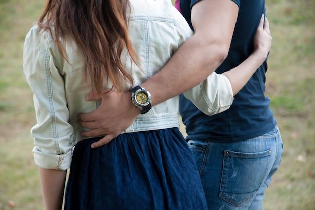彼のガールフレンドの腰に男の手のクローズアップ