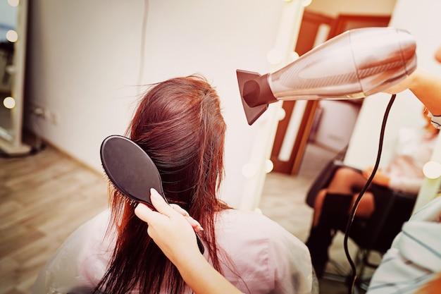 ヘアドライヤー、コンセプトヘアサロン、女性スタイリストのためのヘアドライヤーのクローズアップ。