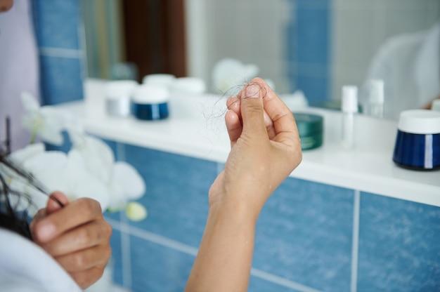 화장실 거울 앞에 서 있는 여성의 손에 있는 탈모의 클로즈업. 건강 관리 개념, 탈모증, 스트레스 및 질병.