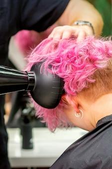Парикмахер сушит короткие розовые или рыжие волосы феном в салоне красоты