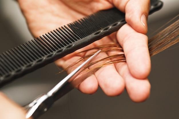 여성의 머리카락을 절단하는 동안 미용사 남성 손의 근접