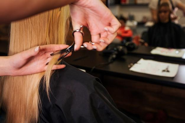 金髪の髪を切る美容師の手のクローズアップ