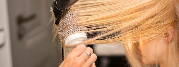 美容師の手のクローズアップは、美容院で金髪の若い女性の髪を乾かしています