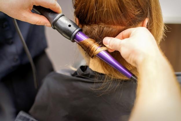Закройте руки парикмахера с помощью щипцов для завивки волос в салоне красоты.