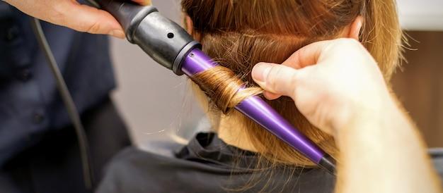 Закройте руки парикмахера с помощью щипцов для завивки волос в салоне красоты. Premium Фотографии