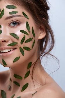 녹색 잎과 완벽한 미소로 절반 여자 얼굴의 클로즈업