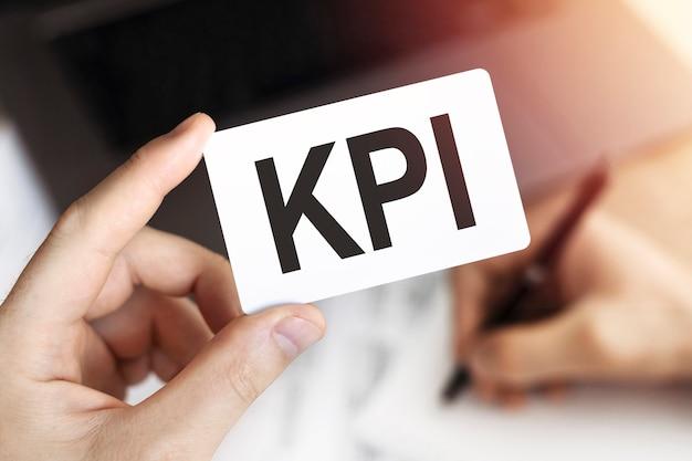 Крупным планом руки деловой человек держит карточку с текстом kpi - ключевые показатели эффективности. документ, ручка и ноутбук.
