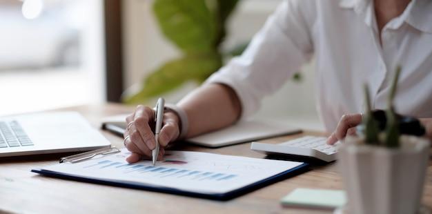 手のクローズアップビジネスウーマンワーキングデータドキュメントグラフチャートレポートマーケティングリサーチ開発計画管理戦略分析財務および会計の概念。