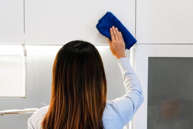 Закройте руки, чистящие белый шкаф тряпкой