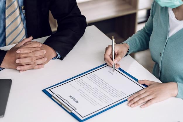 Крупный план женщины работодателя и руки работы, держащей резюме подписания пера в офисе.