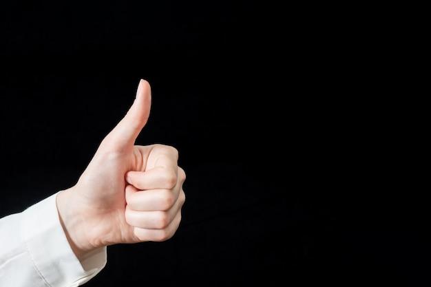 黒の背景に分離された手の指のクローズアップ。白いシャツを着た女性の手は成功の兆しを示しています。ビジネスコンセプト