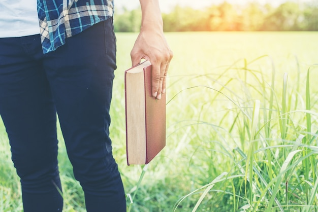 屋外で本を持っている手のクローズアップ