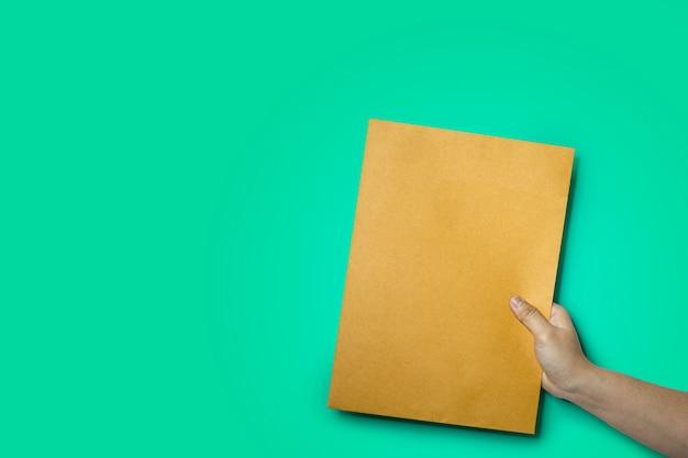 갈색 봉투, a4 크기 종이 봉투, 녹색 배경 및 클리핑 패스에 격리됨을 들고 손을 닫습니다.