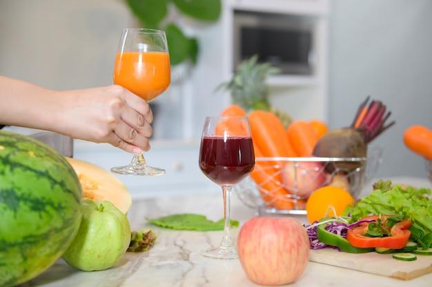 野菜とジューサーキッチン、健康概念のテーブルの上の健康ジュースのガラスを持っている手のクローズアップ