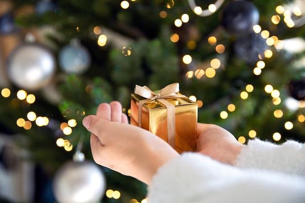 クリスマスツリーとライトが付いている金色のギフトボックスを持っている手のクローズアップ