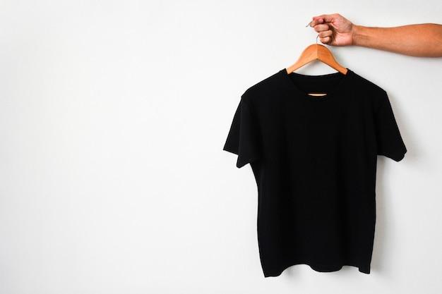 Закройте руки, держащей футболку черного цвета, висящую на деревянной вешалке для ткани на белом фоне, скопируйте пространство