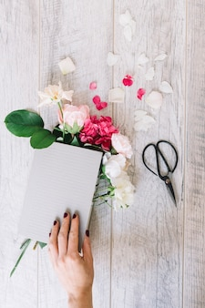 Close-up of hand holding book with hydrangea and roses flowers and scissor on wooden plank