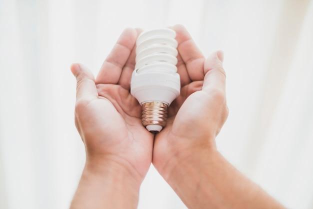 コンパクト、蛍光灯、電球を持つ手のクローズアップ