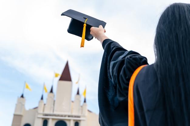 卒業の帽子を持っている手のクローズ アップ